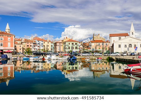 Izola, Slovenia - September 20, 2016: the scenic harbour with boats and brightly coloured houses on the waterfront in Izola.