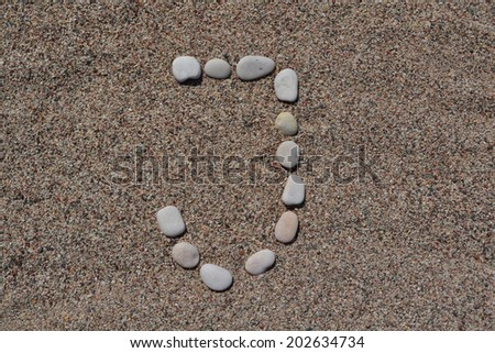 J letter made of stones on sand  - stock photo