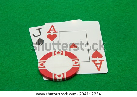 Jack and ace blackjack hand cards with chip on green background - stock photo