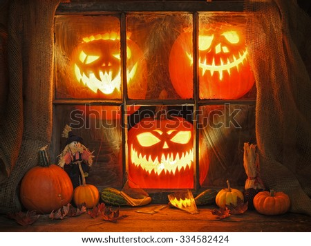 Jack and frightened pumpkins in an old window - stock photo