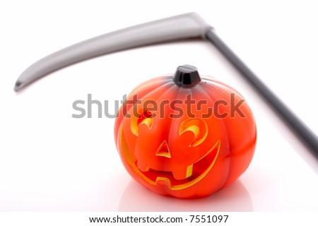 Jack-o-lantern and a scythe blade - stock photo