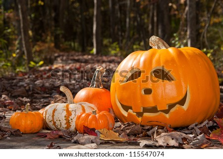 Jack O Lantern and pumpkins on a wood bridge covered with leaves - stock photo