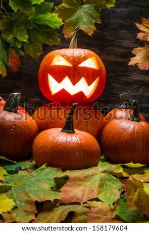 Jack o lantern on pumpkins pile with leaves - stock photo