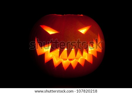 Jack-o'-lantern, smiling Halloween pumpkin glowing in the night. - stock photo