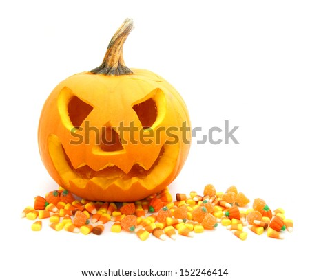 Jack o Lantern with scattered Halloween candy on white background - stock photo