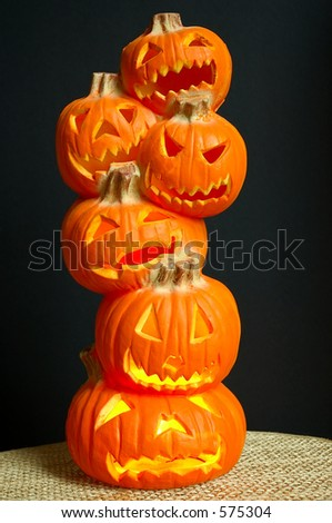 Jack O Lanterns - a stack of pumpkins carved into lighted jack-o-lanterns sitting on a straw mat with black background for Halloween. - stock photo