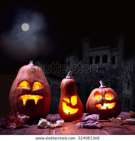 Jack o lanterns Halloween pumpkin face on sinister castle and moon background - stock photo