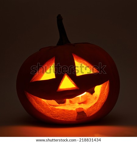 Jack-o'-lanterns orange halloween pumpkin head with the light glowing from the inside, dark low-key composition - stock photo