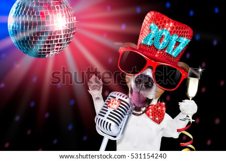 jack russell dog celebrating new years eve with champagne glass and singing out loud, isolated on dark black party nightlife club with retro old microphone