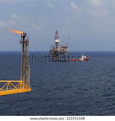 Jack up drilling rig, flare boom, and crew boat in the middle of the sea - stock photo