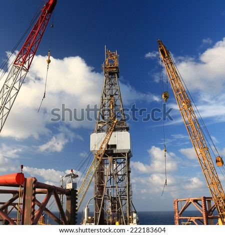 Jack Up Offshore Drilling Rig With Rig Cranes on Sunny Day in The Middle of Ocean - stock photo