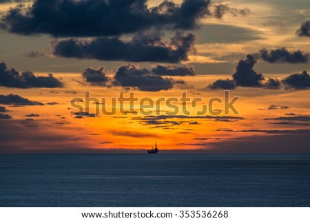 Jack up oil rig in the ocean at twilight time - stock photo