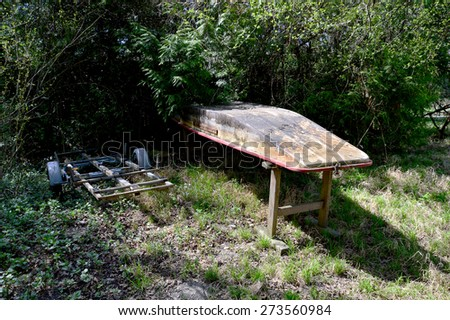 Jacked up Boat and Boat Trailer in a Garden - stock photo