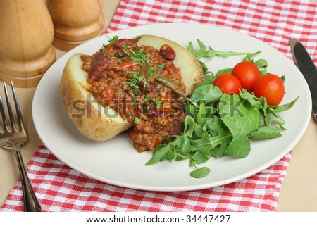 Jacket potato with chilli con carne and herb leaf salad - stock photo