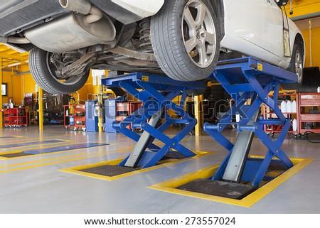 jacks, scissor cranes lift the car in garage - stock photo