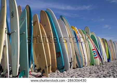 JACKSONVILLE BEACH, FL. USA - JUNE 6, 2015: Surfboards are staged for the Ocean Paddle part of the Never Quit Trident event which involves a 5k Run, 500M Ocean Swim and 1.5k Ocean Paddle. - stock photo