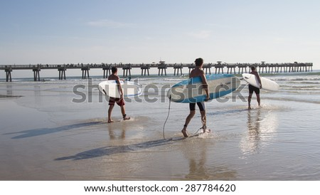 JACKSONVILLE BEACH, FL. USA - JUNE 6, 2015: Unknown athletes begin the Ocean Paddle part of the Never Quit Trident event which involves a 5k Run, 500M Ocean Swim and 1.5k Ocean Paddle. - stock photo