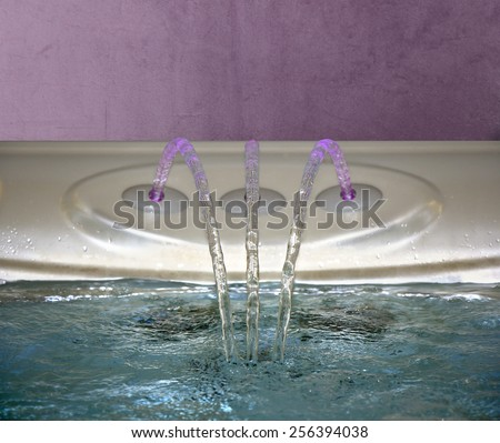 Jacuzzi Bathtub filling up with clean water from a three faucet - stock photo