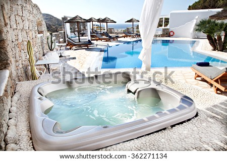 jacuzzi with a swimming pool in background - stock photo