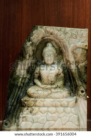 Jade sculpture of buddha isolated on wooden background. - stock photo
