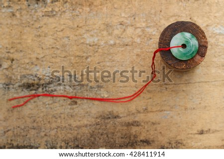 Jade stone with red rope on wooden background. - stock photo