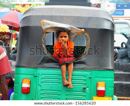 JAFFNA, SRI LANKA - AUG 12: Young girl Asha, 11, sits in the window of her father's traditional taxi on August 12, 2013 in Jaffna, Sri Lanka, South Asia. Tuk-tuk is a popular asian transport as taxi.  - stock photo