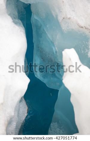Jagged white ice hides a cavern of deep blue ice behind it at Mendenhall Glacier, Alaska - stock photo