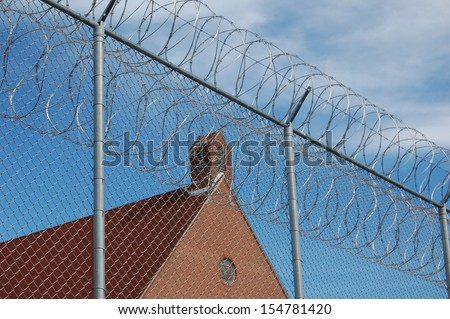 Jail with barbed wire fence - stock photo