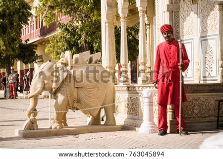 Jaipur, India - 2014, December 29 : A guard standing at the Rajendra Pol entrance gate to the City Palace complex next to a marble elephant sculpture
