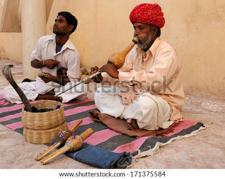 JAIPUR, INDIA - FEBRUARY 20: A snake charmer is playing the flute for the cobra sitting by the wall in the Fort Amber on February 20, 2010 in Jaipur, India