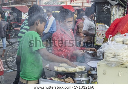 Jaipur, India - February 27, 2014 - Street food vendor preparing meal and snack for customers at local market during daytime