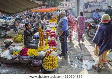 Jaipur, India - February 27, 2014 - Vendors selling fresh flowers and garlands at local market of Jaipur during bright sunny day
