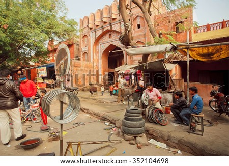 JAIPUR, INDIA - JAN 25: Technician workers repairing wheels for cars and bicycles in a street shop of indian city on January 25 2015. Jaipur, with population 6,664000 people, is a capital of Rajasthan - stock photo