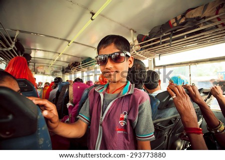 JAIPUR, INDIA - JAN 19: Unidentified boy smiling inside the public bus with many Indian passengers on January 19, 2015. Jaipur, with population 6,664000 people, is a capital of Rajasthan
