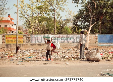JAIPUR, INDIA - JAN 21: Unidentified poor children collect rubbish on the streets for recycling on January 21, 2015 in Rajasthan. Jaipur, with population 6,664,000 people, is a capital of Rajasthan - stock photo