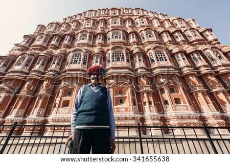 JAIPUR, INDIA - JANUARY 10, 2015: Indian senior man near Hawa Mahal palace (Palace of the Winds) on January 10, 2015 in Jaipur, Rajasthan, India - stock photo