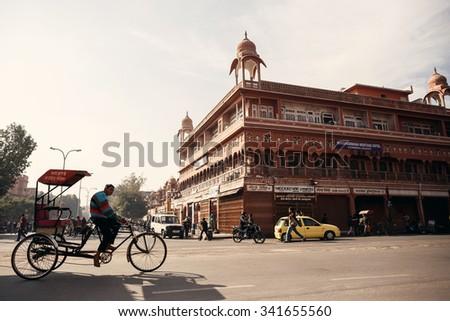 JAIPUR, INDIA - JANUARY 10, 2015: Man riding cycle rickshaw on street on January 10, 2015 in Jaipur, India - stock photo