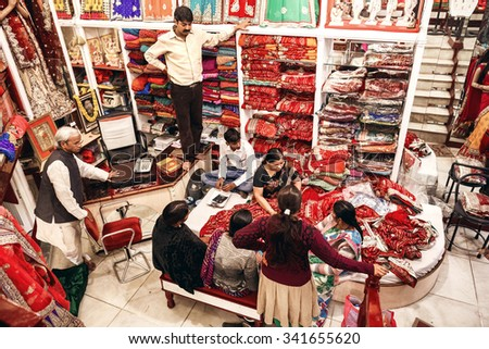 JAIPUR, INDIA - JANUARY 9, 2015: People in local textile shop of traditional indian sari on January 9, 2015 in Jaipur, India - stock photo