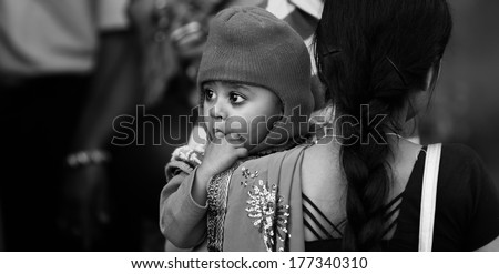 JAIPUR, INDIA � MARCH 4: An unidentified child held by his mother outside the City Palace on March 4, 2012 ahead of the annual Holi Festival in Jaipur, Rajasthan, Northern India. - stock photo