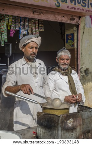 Jaipur, India - March 1, 2014 - Men preparing hot milk tea Indian style or chai  for customers from his shop along street