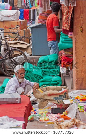 JAIPUR, INDIA - MARCH 26, 2014: Street traders in the Tripolia Bazaar lay out their merchandise at the edge of the sidewalk. Space is at a premium in the market