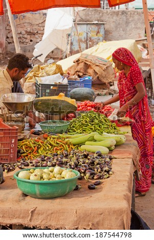 JAIPUR, INDIA - MARCH 26, 2014: Trader and customer in the fruit and vegetable market in the Johari Bazaar district of the old city - stock photo