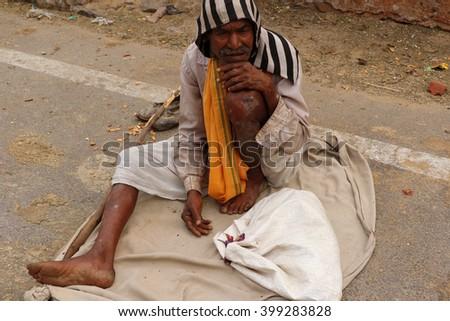 Jaipur, India - March 25, 2016: Unknown beggar man is begging on roadside near Galtaji temple, Jaipur. - stock photo