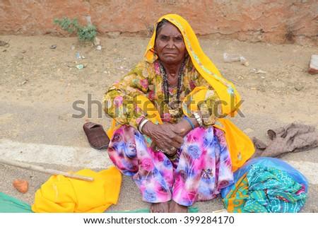 Jaipur, India - March 25, 2016: Unknown beggar woman is  begging on roadside near Galtaji temple, Jaipur. - stock photo