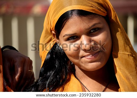 Jaipur, India, November 30, 2012: Beautiful Indian girl with traditional colorful sari, looking at the camera, in the Indian Rajasthan state - stock photo