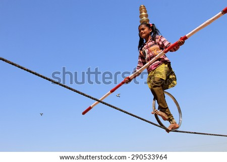 JAISALMER, INDIA - FEB 03, 2015: An unidentified Indian girl performs street acrobatics by walking the rope during the Desert Festival on February 03,2015 in Jaisalmer, Rajasthan, India. - stock photo