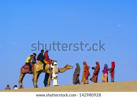 JAISALMER, INDIA-FEB 25: Camel riding at Sam Sand Dune on Feb 25, 2013 in Jaisalmer, India.The activity is part of Desert Festival held in winter to attract both domestic and international tourists. - stock photo