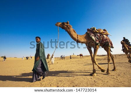 JAISALMER, INDIA - FEB 25:  Cameleer at the Sam Sand Dune on Feb 25, 2013 in Jaisalmer, India.  Apart from farming, camel riding activity for tourists is another income source for desert villagers - stock photo