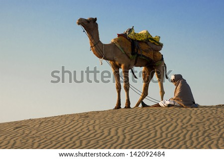 JAISALMER, INDIA-FEB 26: Cameleer waits for tourists at Sam Sand Dune on Feb 26, 2013 in Jaisalmer, India. Apart from farming, camel riding activity is another income source for desert villagers - stock photo