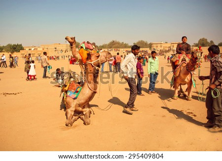 JAISALMER, INDIA - FEB 1: Rural landscape and villagers with camels riding animals during the Desert Festival of Rajasthan on February 1, 2015. Every winter Jaisalmer takes the famous Desert Festival